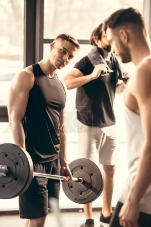 Photo for Muscular handsome young men exercising together in gym - Royalty Free Image