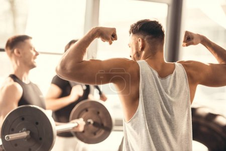 back view of young sportsman showing muscles to friends in gym