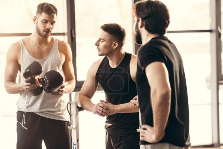 three athletic young men on sportswear talking in gym