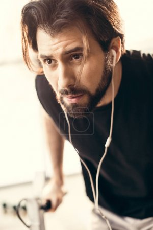 close-up view of bearded young sportsman training and looking away in gym