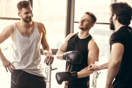 three sporty young men on sportswear talking in gym