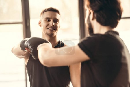 selective focus of young athletes in boxing gloves greeting each other in gym