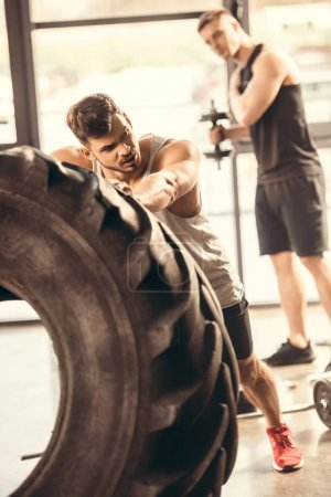 athletic young man in sportswear exercising with tire in gym