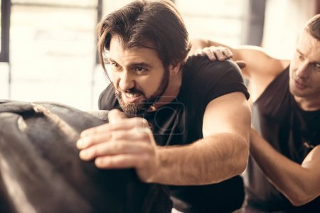 focused sporty young man lifting tyre in gym