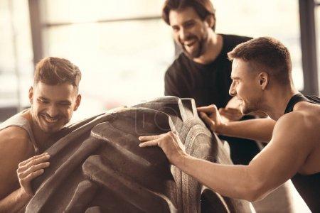 joyeux jeunes hommes sportifs s'entraînant avec des pneus dans la salle de gym