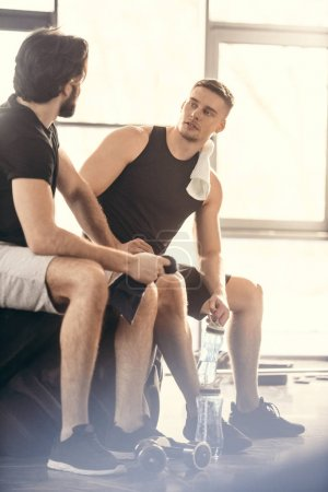 two young sportsmen sitting on tire and looking at each other after workout in gym