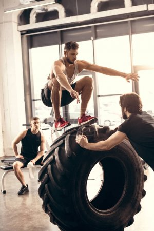 athletic young man jumping on tire while training with friends in gym