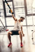 athletic young man in sportswear exercising with suspension straps in gym