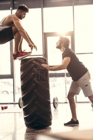 side view of muscular young men in sportswear training with tire in gym