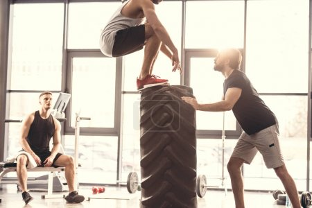 cropped shot of sporty young men exercising with tyre in gym