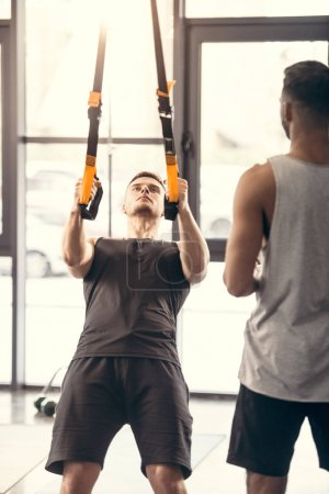 Photo for Cropped shot of sporty man looking at muscular man training with suspension straps in gym - Royalty Free Image