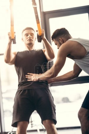 trainer helping young sportsman exercising with suspension straps in gym