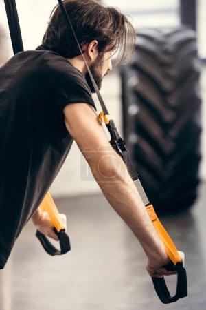 Photo pour Vue latérale de l'athlétique jeune homme de formation avec des sangles de remise en forme dans la salle de gym - image libre de droit