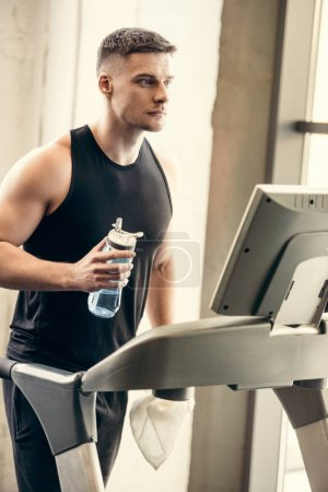 sporty young man holding bottle of water and training on treadmill