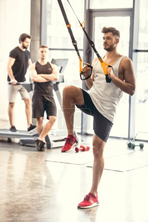 full length view of muscular young man training with resistance bands in sports center