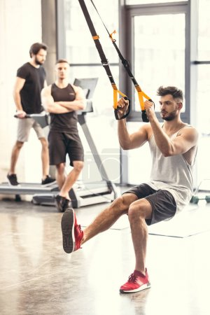 Photo for Handsome muscular young man training with resistance bands in sports center - Royalty Free Image