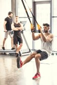 handsome muscular young man training with resistance bands in sports center