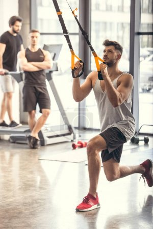 athletic young man training with resistance bands in sports center
