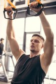 handsome athletic young man exercising with fitness straps and looking away in gym