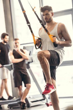 Photo for Handsome sporty young man training with suspension straps in gym - Royalty Free Image