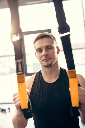 Photo for Handsome young man training with fitness straps and looking at camera in gym - Royalty Free Image