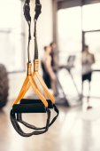 close-up view of fitness straps and young sportsmen standing behind in gym