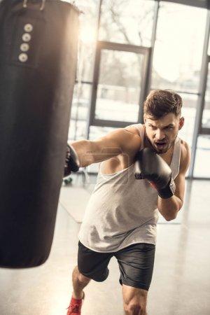 Photo pour Entraînement émotionnel jeune sportif avec sac de boxe dans la salle de gym - image libre de droit