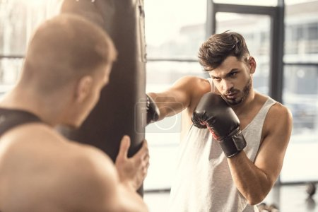 selective focus of sportsmen training with punching bag in gym
