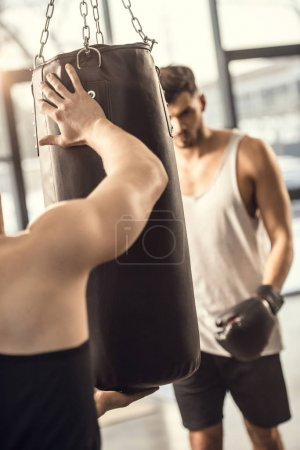 selective focus of trainer holding punching bag while boxer training in gym