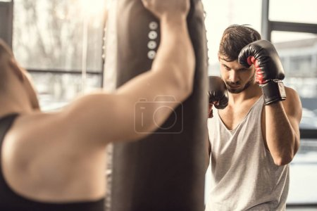 cropped shot of trainer holding punching bag while boxer training in gym