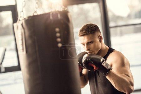 Photo pour Athlétique jeune homme en gants de boxe, entraînement avec sac de boxe dans la salle de gym - image libre de droit