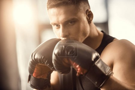 handsome focused young sportsman in boxing gloves training in gym