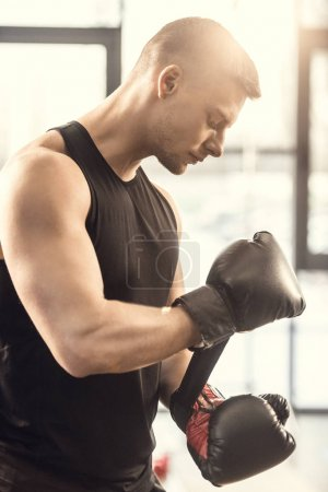 side view of muscular young sportsman wearing boxing gloves