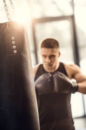 selective focus of athletic young man boxing with punching bag