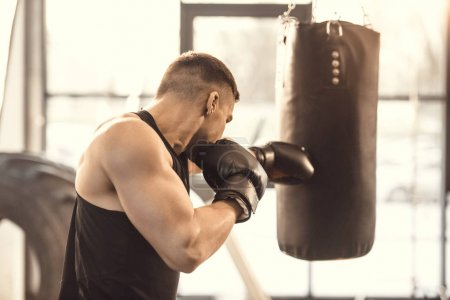 side view of muscular young boxer training with punching bag