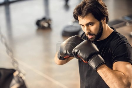 handsome focused young man in boxing gloves exercising in sports center
