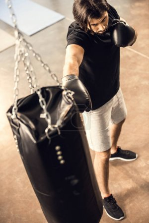 high angle view of sporty young man boxing with punching bag in gym