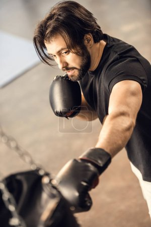 high angle view of muscular young man boxing in gym