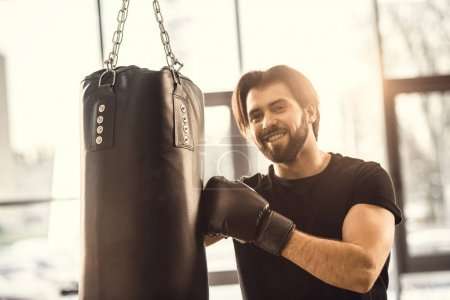 handsome young man boxing and smiling at camera in gym