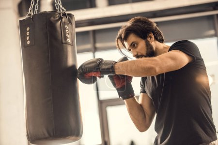 Photo for Side view of handsome young man boxing in sports center - Royalty Free Image