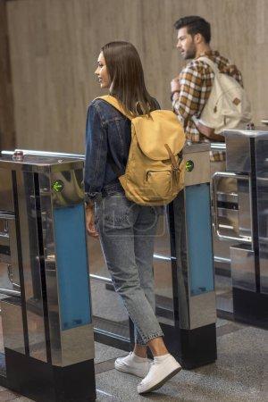 Photo pour Couple d'élégants touristes avec sacs à dos, en passant par les tourniquets - image libre de droit