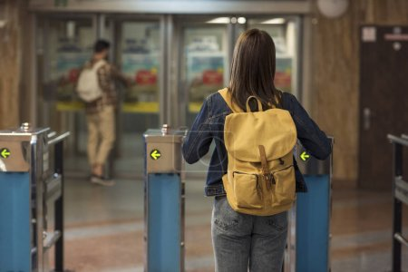 rear view of female stylish traveler with backpack passing through turnstiles and male tourist behind
