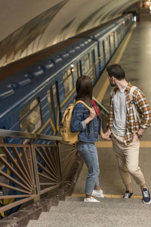stylish travelers with backpacks standing on stairs at subway station