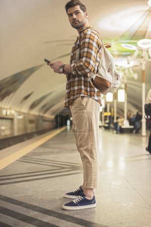 stylish man with backpack and smartphone at subway station