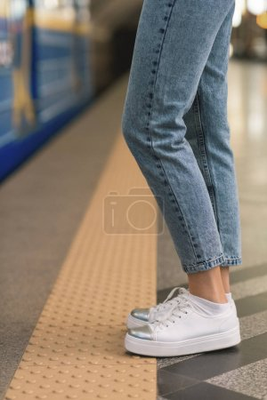 cropped image of female legs in stylish jeans and sneakers at subway station