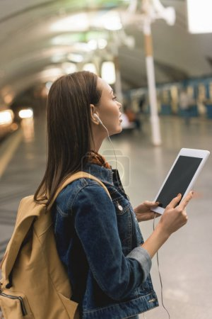 stylish woman with earphones and digital tablet at subway station