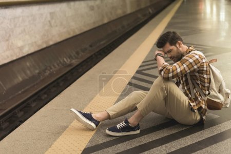 upset young man with backpack late on train and sitting on floor at subway station