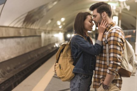 side view of female traveler embracing boyfriend at subway station