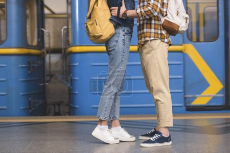 cropped image of stylish couple of tourists embracing each other at subway station
