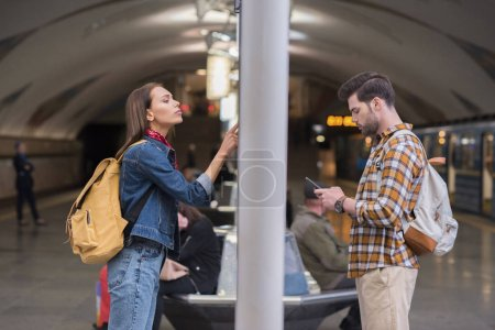 side view of female traveler with backpack looking at information board and boyfriend using smartphone at subway station